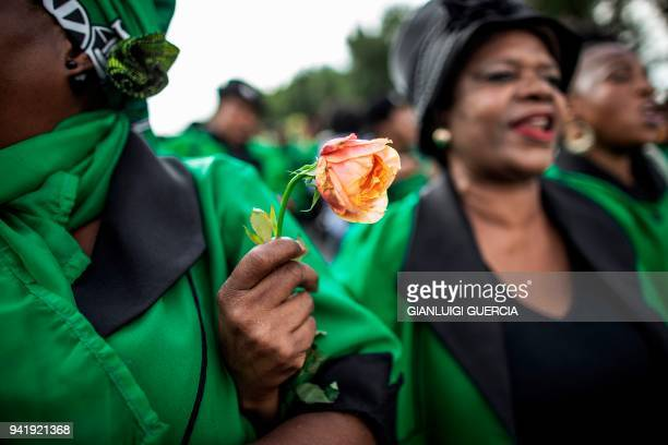 Members of the African National Congress Women's League hold flowers as they rally outside the home of the late South African antiapartheid...