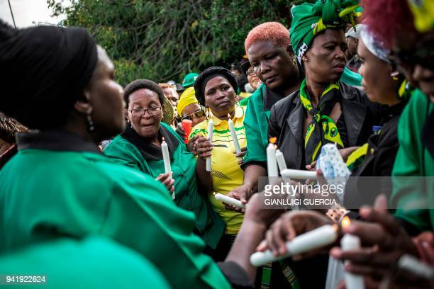 Members of the African National Congress Women's League light candles as they gather outside the home of the late South African antiapartheid...