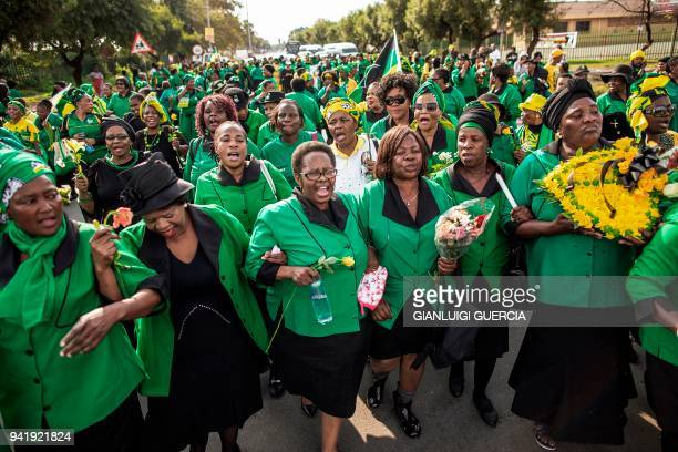 TOPSHOT Members of the African National Congress Women's League march holding flowers to lay outside the home of the late South African antiapartheid...