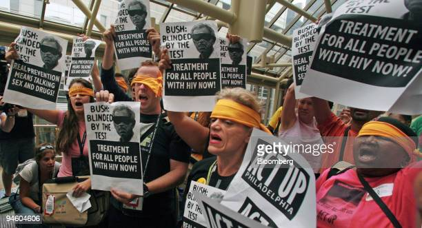Members of the AIDS activist group ACT UP participate in a protest against US AIDS testing policies outside the press center at the 16th...
