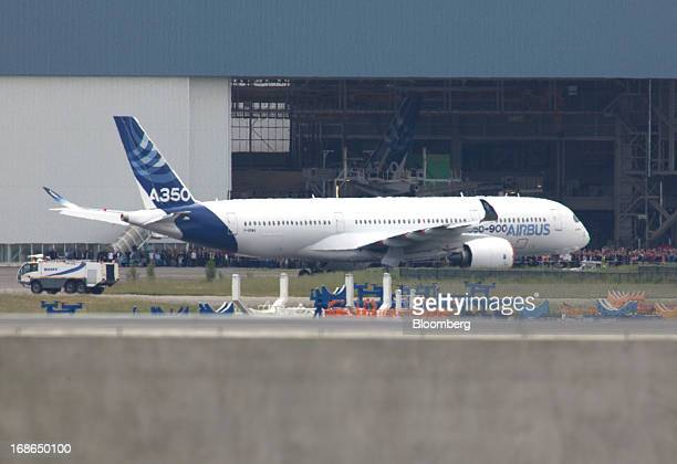 Members of the Airbus workforce stand and watch as the new Airbus A350 XWB aircraft built by Airbus SAS a unit of European Aeronautic Defence Space...
