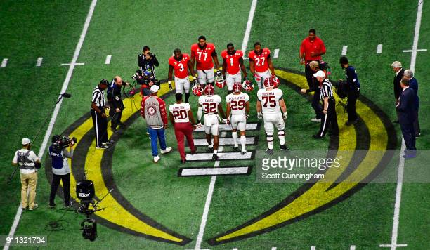 Members of the Alabama Crimson Tide and the Georgia Bulldogs participate in the coin toss before the CFP National Championship presented by ATT at...