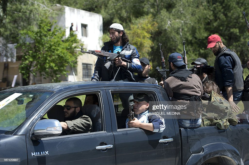 Members of the Al-Ezz bin Abdul Salam brigade hold their weapons sitting in the back of an open pickup truck on their way from al-Rabeea to the al-Turkman mountains in the Latakia province, western Syria on April 25, 2013.
