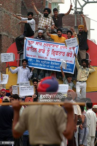 Members of the All India Sikh Student Federation block the railway tracks in protest against the chief of the spiritual organisation Dera Sacha...