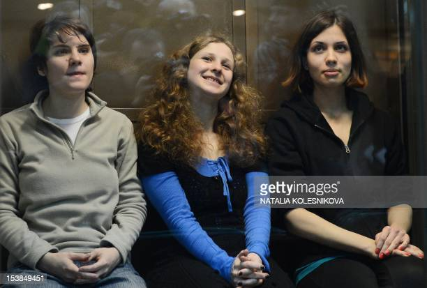 Members of the allgirl punk band Pussy Riot Maria Alyokhina Yekaterina Samutsevich and Nadezhda Tolokonnikova sit in a glasswalled cage in a court in...
