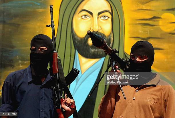 Members of the alMehdi Army militia loyal to the radical Shiite cleric Moqtada alSadr stand in front of a picture of Imam Ali on August 7 2004 at a...
