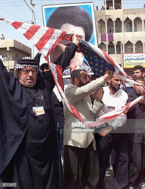 Members of the alMehdi Army militia rip up an Americna flag during a military parade through the streets of the Sadr City neighborhood in East...