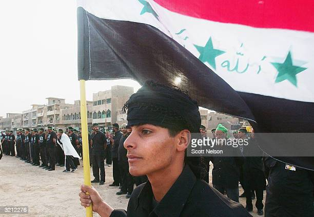 Members of the alMehdi Army stand to attention prior to a military parade through the streets of the Sadr City neighborhood in East Baghdad on April...