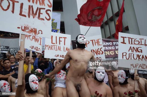 Members of the Alpha Phi Omega display placards as they run around naked in the Arts and Sciences building in the traditional Oblation Run to...