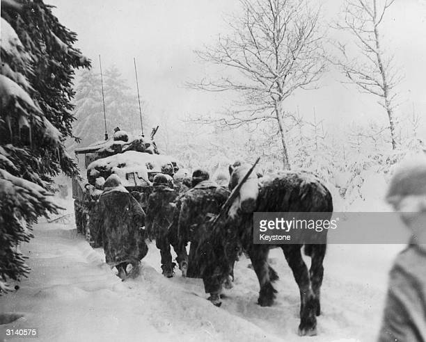 Members of the American 82nd Airborne Division trudging through the snow behind a tank during the Battle of the Bulge.