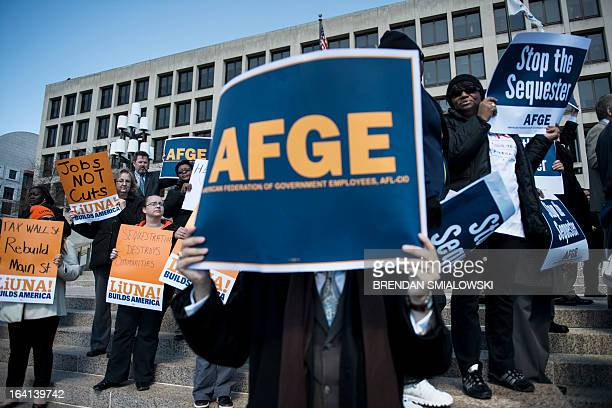 Members of the American Federation of Government Employees and members Laborers International Union of North America gather during a rally on outside...