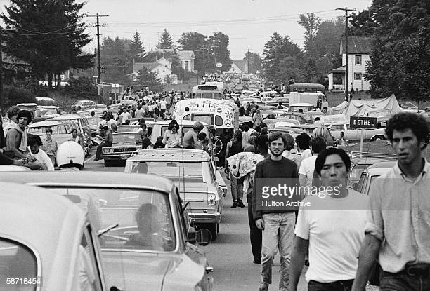 Members of the American youth subculture generally termed 'hippies' walk along roads choked with traffic on the way to the large rock conert called...