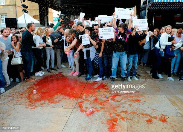 Members of the animal protection association '269 Life Liberte Animale' pour fake blood as they demonstrate at the start of a speech by Farright...