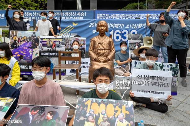 Members of The Anti-Abe Anti-Japanese Youth Student Joint Action , tie each other's bodies with a rope and sit down and hold banners written as...