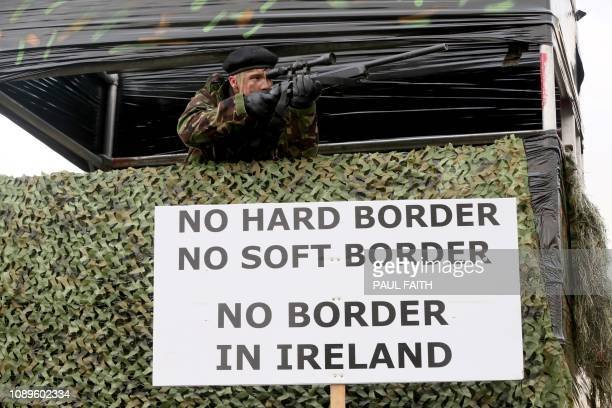 Members of the antibrexit campaign group Border communities against Brexit dressed as British Army Soldiers pose with a wall installed on a road...