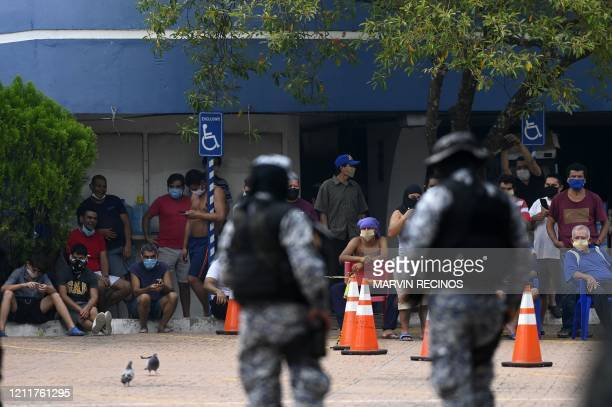 Members of the AntiRiot Unit and the Tactical Operations System of the National Civil Police guard quarantined people in a containment centre where...