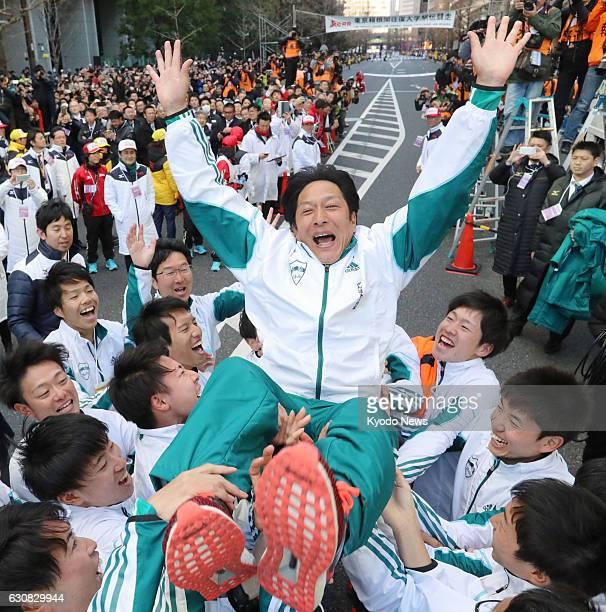 Members of the Aoyama Gakuin University Tokyo-Hakone collegiate ekiden road relay team toss their manager Susumu Hara in the air on Jan. 3 in Tokyo,...