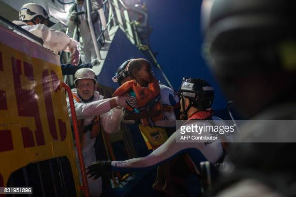 TOPSHOT Members of the Aquarius rescue ship run by NGO SOS Mediterranee and Medecins Sans Frontieres help a child after he was rescued by the NGO...