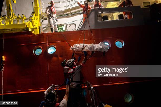 TOPSHOT Members of the Aquarius rescue ship run by nongovernmental organisations SOS Mediterranee and Medecins Sans Frontieres prepare to load a body...