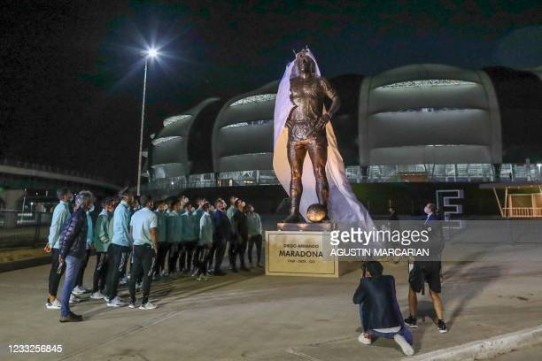 Members of the Argentine national football team and the president of the Argentine Football Association , Claudio Tapia, unveil a five-metre statue...