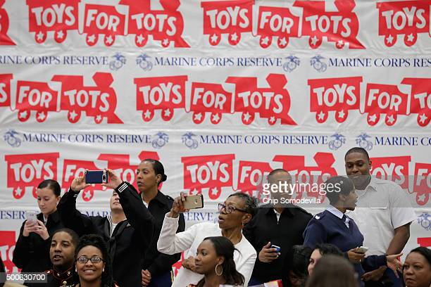 Members of the armed forces and their families photograph US first lady Michelle Obama as she helps distribute donations to the US Marine Corps...