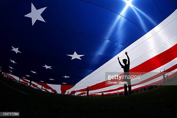 Members of the armed forces hold a giant American flag during the national anthem prior to the season opener between the San Diego Chargers and the...