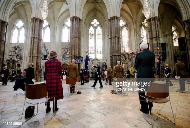 Members of the armed forces of Australia and New Zealand hold their respective national flags as they process through the nave during a service of...