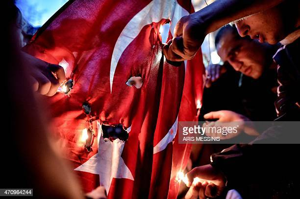 Members of the Armenian community set fire to the Turkish flag during a gathering to commemorate the 100th anniversary of the Armenian genocide in...