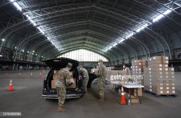 Members of the Army National Guard load food into the back of a car at the Kingsbridge Armory, which is being used as a temporary food distribution...