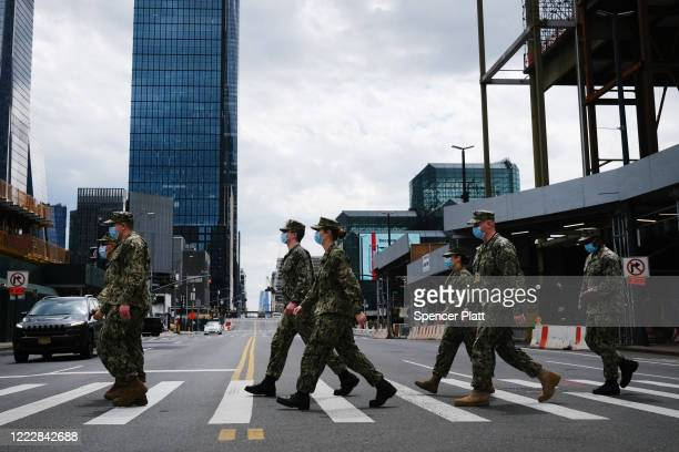 Members of the Army National Guard who have been called into Manhattan to help combat the coronavirus cross the street on May 04 2020 in New York...