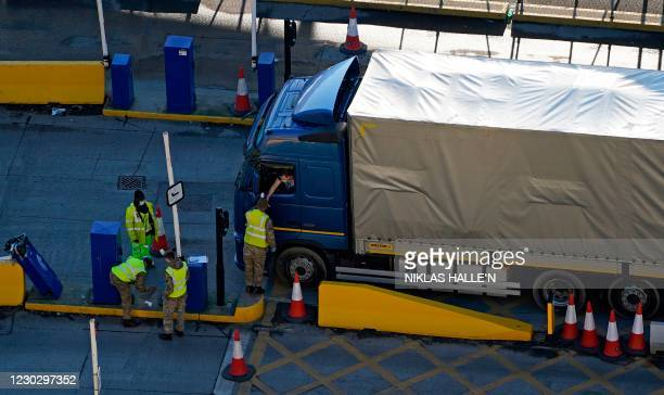 Members of the Army talk to a lorry driver arriving at the Port of Dover, in Dover on the south-east coast of England, on December 25 as the COVID-19...