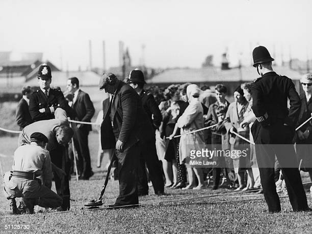 Members of the army's bomb disposal unit use metal detectors to search for clues near Braybrook Street Shepherd's Bush 13th August 1966 Three...
