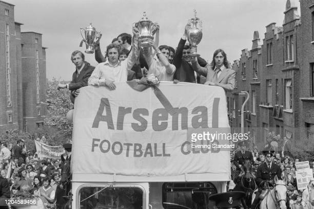 Members of the Arsenal FC team hold up trophies, including the League championship trophy and FA Cup trophy, as they parade in an open top bus...