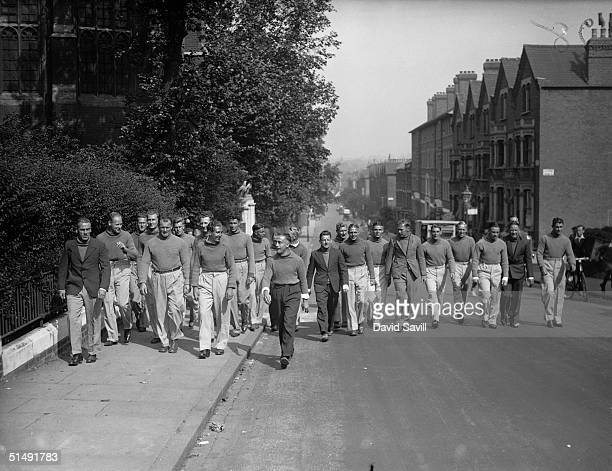 Members of the Arsenal Football Club squad walking up Highbury Hill on their first day of training for the upcoming season 6th August 1935