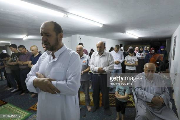 Members of the Ashour family gather in prayer at a family home due to closure of mosques during the coronavirus pandemic in the flashpoint city of...