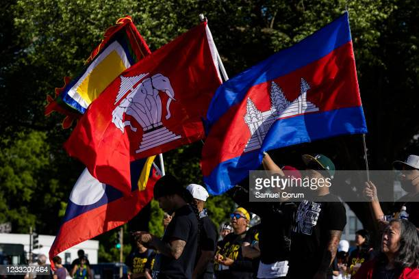 Members of the Asian American and Pacific Islander community and their allies hold up flags during a rally on the National Mall on May 31, 2021 in...