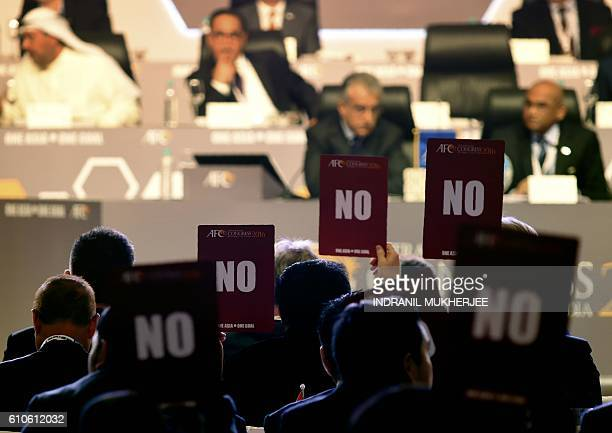 Members of the Asian Football Confederation hold up 'NO' voting cards during the AFC Extraordinary Congress in Goa on September 27, 2016. An Asian...