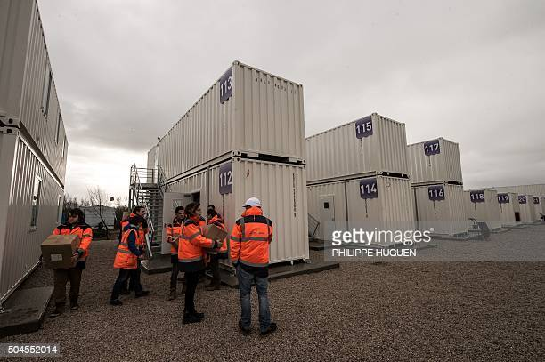 Members of the association 'La vie active' are a work next to shipping container converted into homes on January 11 2016 in Calais northern France...
