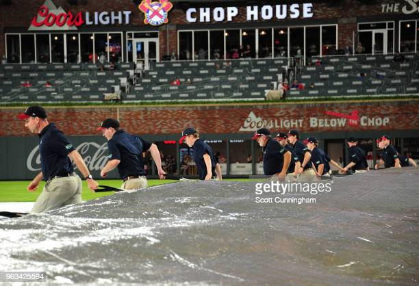 Members of the Atlanta Braves grounds crew remove the tarp after a three hour rain delay for the game against the New York Mets at SunTrust Field on...