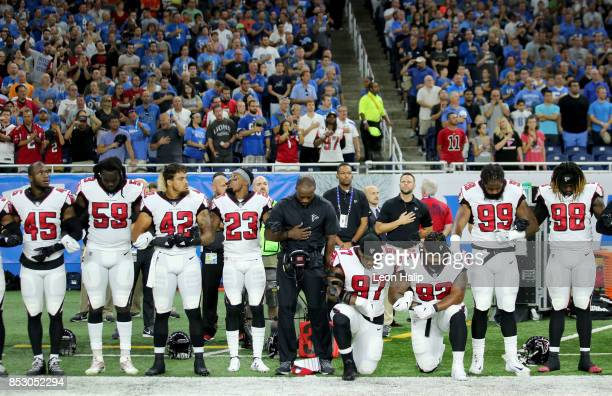 Members of the Atlanta Falcons football team Grady Jarrett and Dontari Poe take a knee during the playing of the national anthem prior to the start...