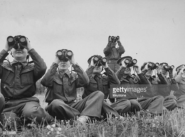 Members of the ATS with binoculars watch aircraft take off and land on an airfield, during recognition tests at a training school in the south of...
