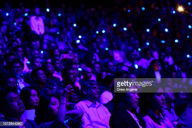 Members of the audience are bathed in blue light as they watch a presentation for the new Samsung Galaxy Note 9 smartphone during a product launch...