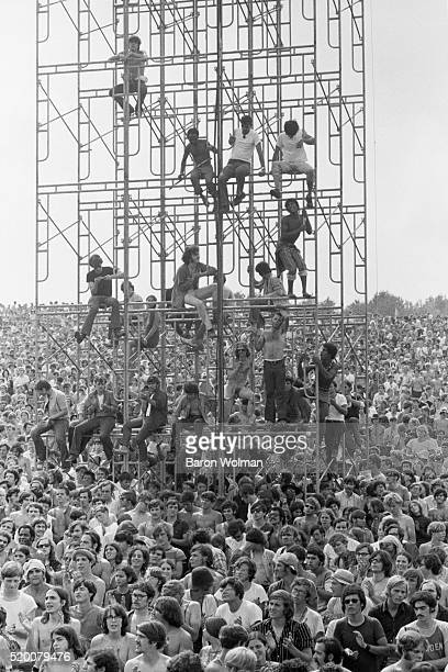 Members of the audience climb the sound tower to secure a better view at the Woodstock Music Art Fair Bethel NY August 15 1969