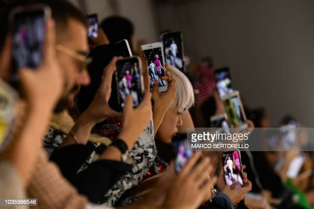 Members of the audience film with their phones models presenting creations by Annakiki during the Women's Spring/Summer 2019 fashion shows in Milan...