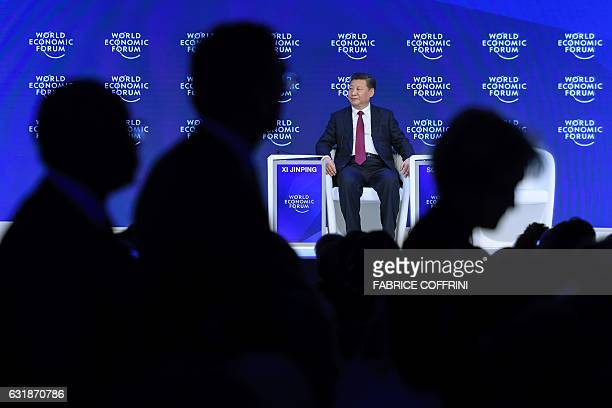 Members of the audience leaves the room as China's President Xi Jinping sits after delivering a speech during the first day of the World Economic...
