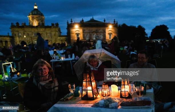Members of the audience sit around a candlelit table during the annual Castle Howard Proms Spectacular concert held on the grounds of the Castle...