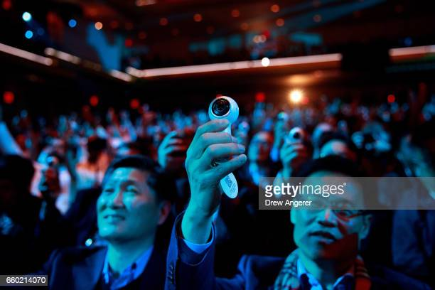 Members of the audience take photos as they hold up a new version of the Samsung Gear 360 camera which was distributed to the crowd during a launch...