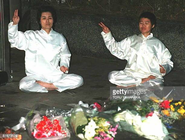 Members of the Aum Shinrikyo sit on the ground to perform a rite 24 April to pay tribute to the late Science and Technology minister of the sect...