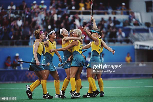 Members of the Australia Women's Field Hockey team celebrate after scoring a goal in their medal round match against New Zealand in the Women's field...