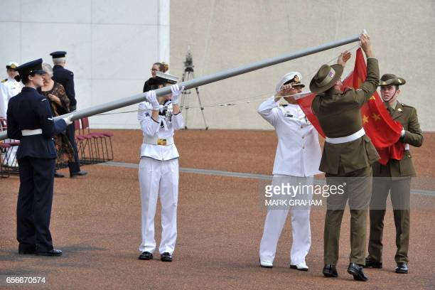 Members of the Australian Federation Guard adjust the Chinese national flag before the ceremonial welcome of China's Premier Li Keqiang at Parliament...
